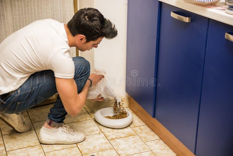 Jonge Mens het Vullen Huisdierenkom met Droog Voedsel stock afbeelding