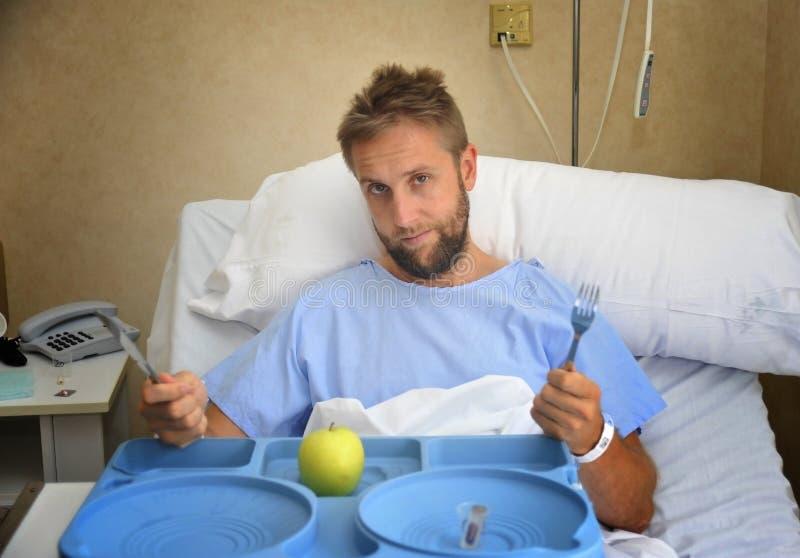 Jonge mens in het ziekenhuisruimte na het lijden van aan ongeval die gezond humeurig en droevig de kliniekvoedsel eten van het ap royalty-vrije stock afbeeldingen