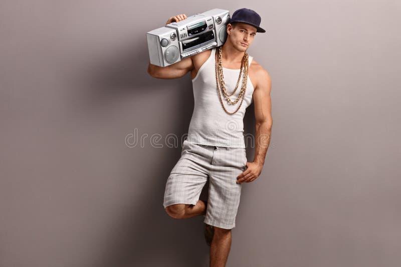 Jonge mens in hiphopkleren die een stereo-installatie dragen stock foto's