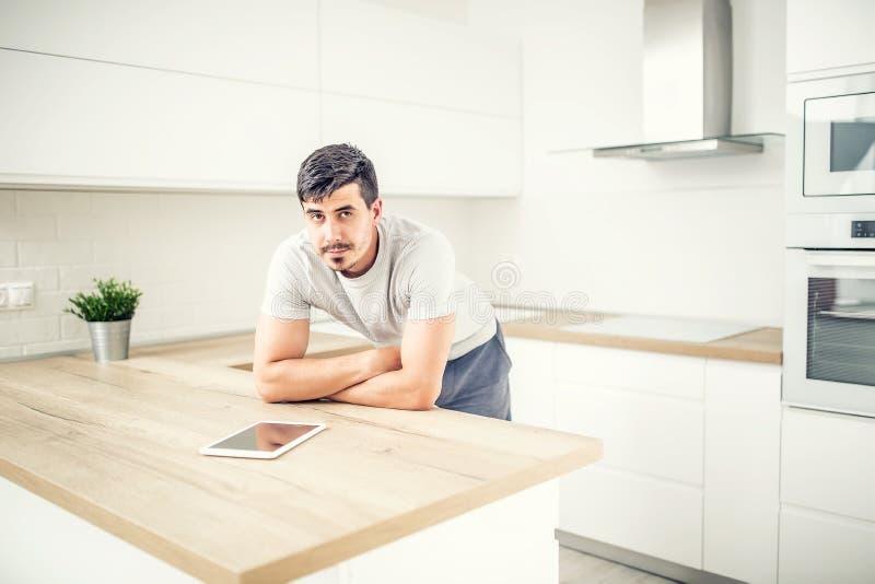 Jonge mens in huiskeuken met tablet stock foto