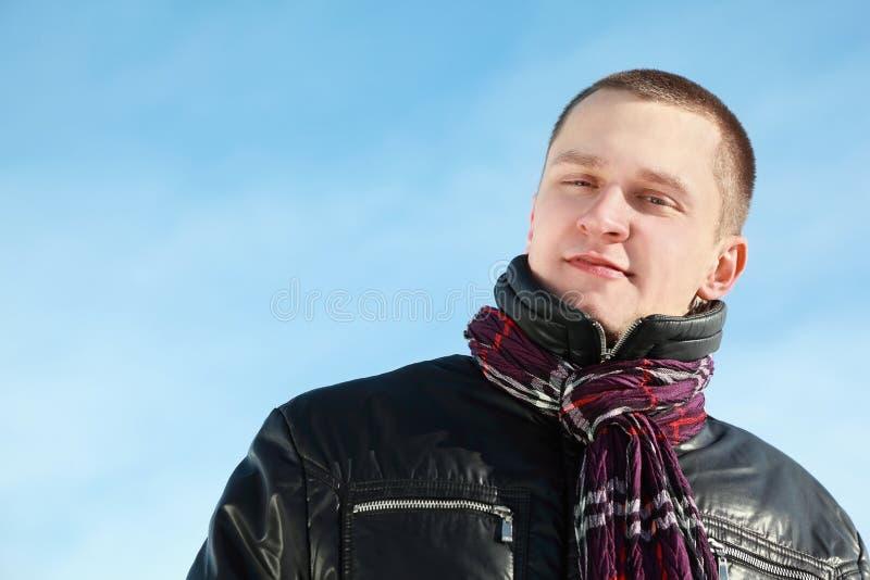 Jonge mens in jasjetribunes tegen de winterdag stock foto's