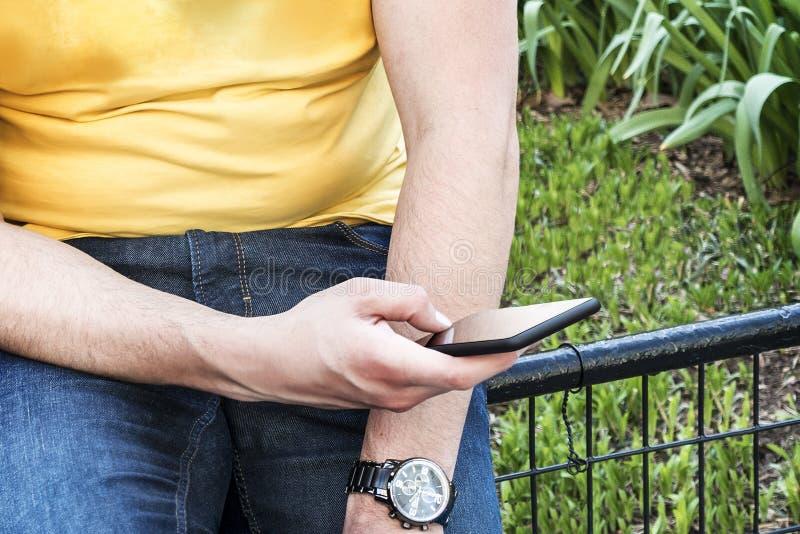 Jonge mens in jeans en gele t-shirt die zijn smartphone gebruiken stock foto