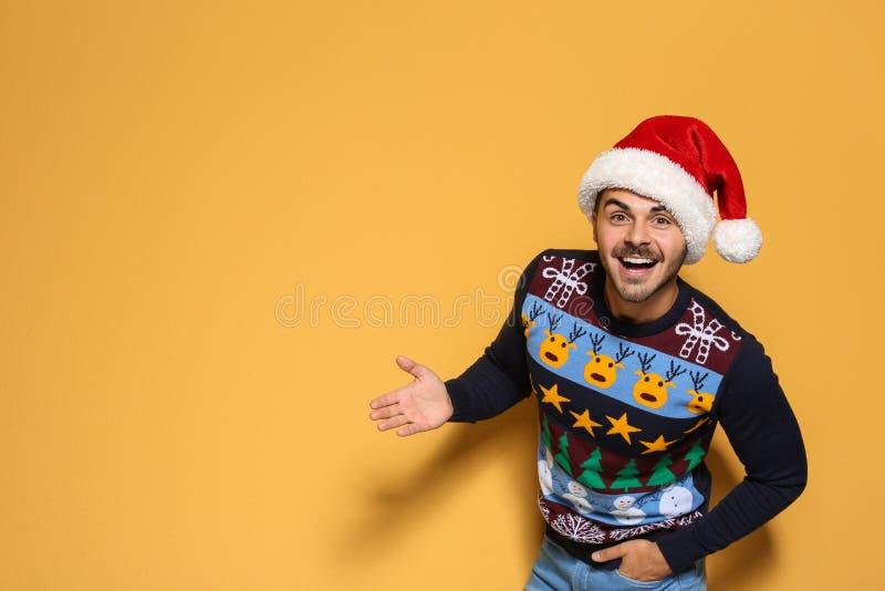 Jonge mens in Kerstmissweater en hoed op kleurenachtergrond royalty-vrije stock afbeeldingen