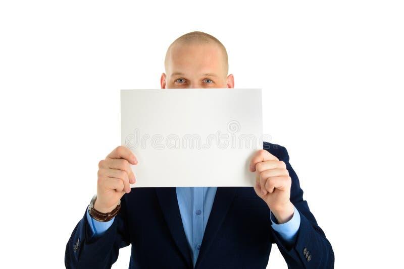 Jonge mens in kostuum met een leeg blad van document half behandelend die gezicht op wit wordt geïsoleerd stock afbeeldingen