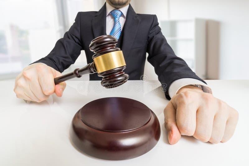 Jonge mens in kostuum met hamer in bureau Veiling of rechtvaardigheidsconcept stock afbeelding