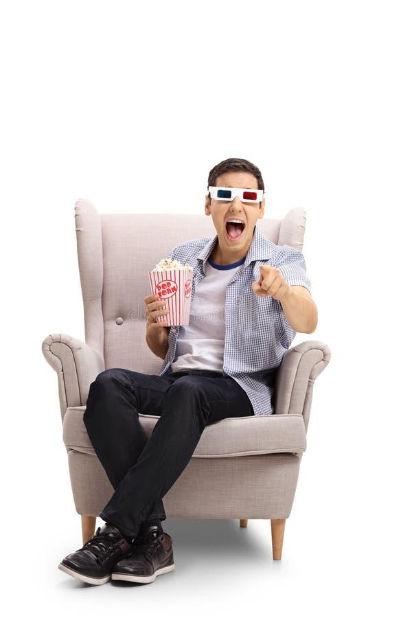 Jonge mens met 3D glazen en popcorn gezet in een leunstoel laug royalty-vrije stock foto