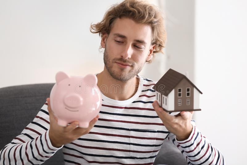 Jonge mens met de modelzitting van het spaarvarken en van het huis in leunstoel thuis stock fotografie