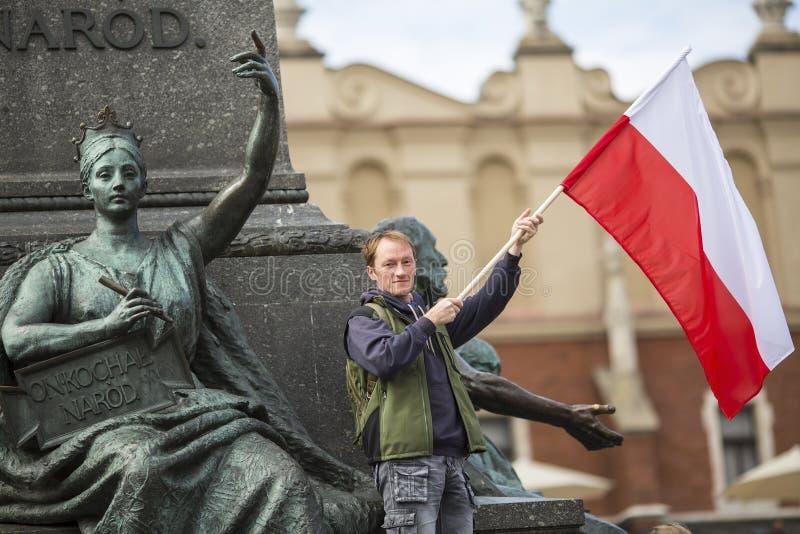 Jonge mens met de Poolse vlag dichtbij Mickiewicz-monument in het belangrijkste vierkant van Krakau royalty-vrije stock foto