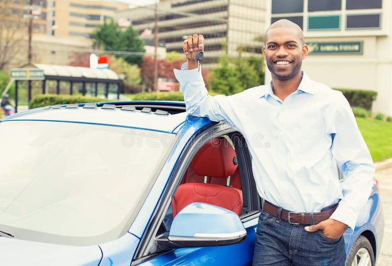 Jonge mens met de sleutels die zich door zijn nieuwe auto bevinden stock foto