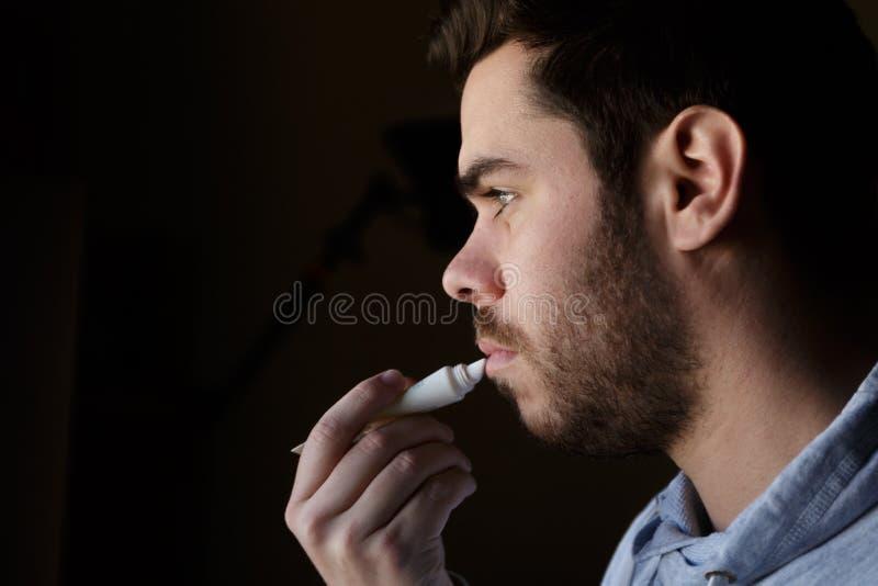 Jonge mens met een baard die zijn beschadigde lippen met vochtinbrengende crème herstellen royalty-vrije stock foto's