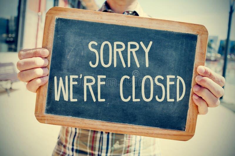 Jonge mens met een bord met de droevige tekst zijn wij gesloten, F royalty-vrije stock fotografie