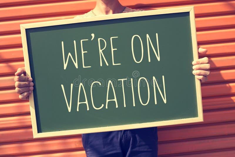 Jonge mens met een bord met de tekst zijn wij op vakantie, FI royalty-vrije stock afbeelding