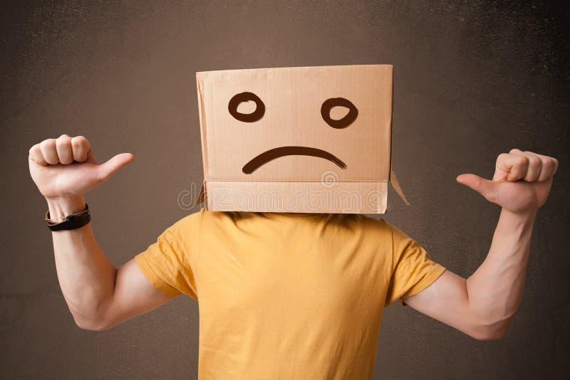 Jonge mens met een bruine kartondoos op zijn hoofd met droevig gezicht vector illustratie