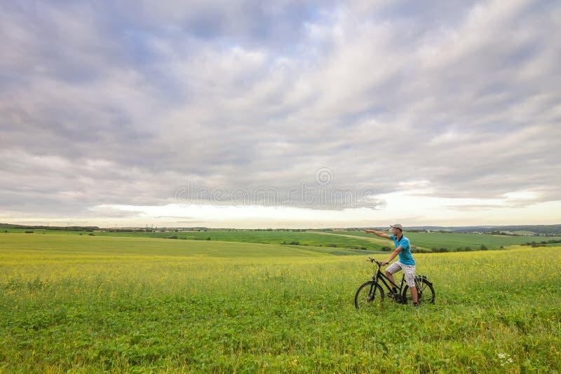Jonge mens met een fiets op groen gebied op een zonnige de zomerdag stock foto