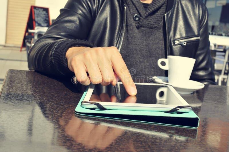 Jonge mens met een kop van koffie die een tablet in het terras gebruiken van stock fotografie
