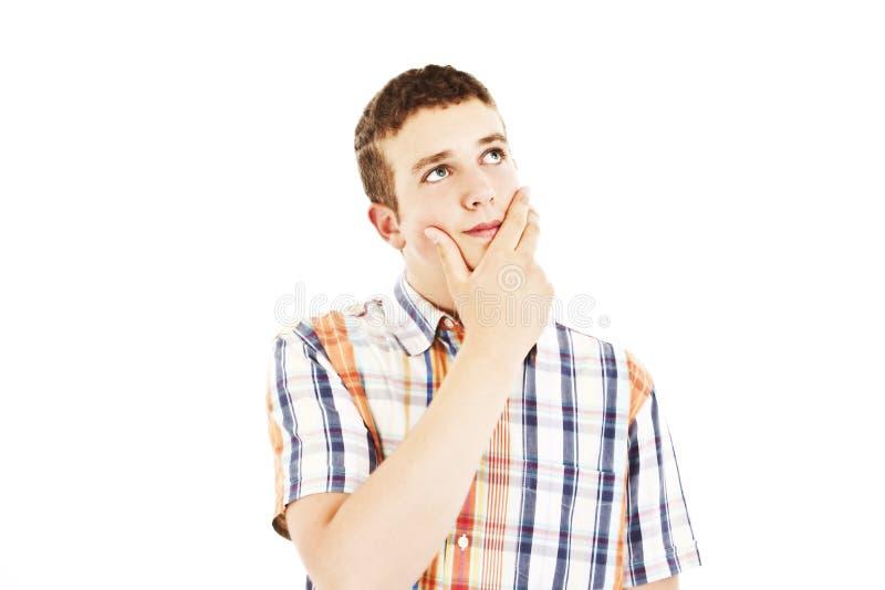 Jonge mens met een peinzende uitdrukking die omhoog eruit ziet royalty-vrije stock afbeelding