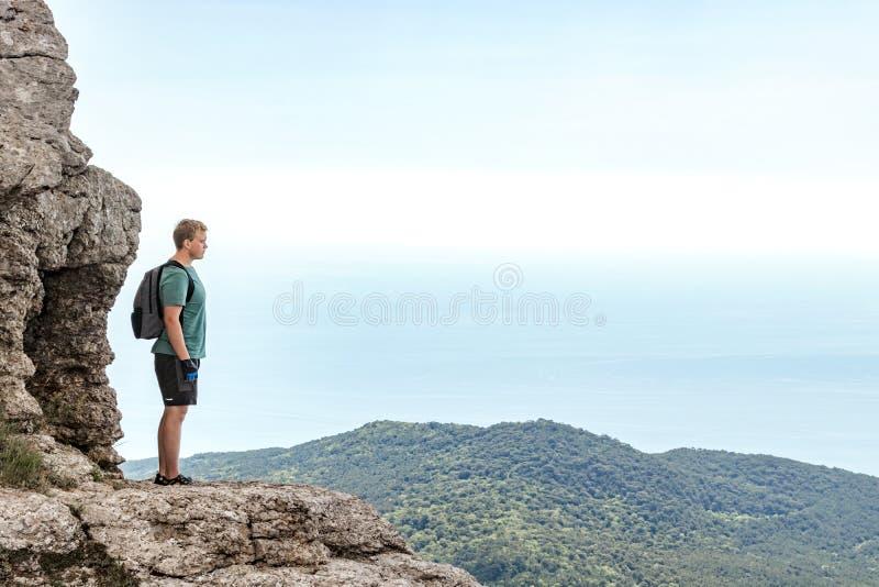 Jonge mens met een rugzak bovenop klip die van mening van aard genieten Bergen en Overzees royalty-vrije stock fotografie