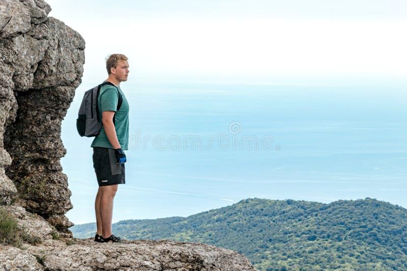 Jonge mens met een rugzak bovenop klip die van mening van aard genieten Bergen en Overzees stock afbeeldingen
