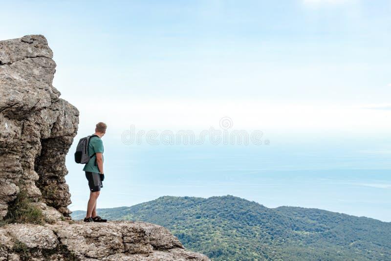Jonge mens met een rugzak bovenop klip die van mening van aard genieten Bergen en Overzees royalty-vrije stock foto's
