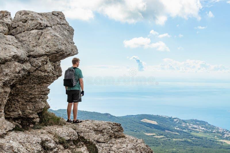Jonge mens met een rugzak bovenop klip die van mening van aard genieten Bergen en Overzees royalty-vrije stock afbeelding
