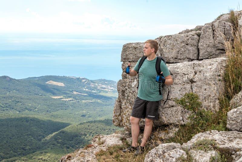 Jonge mens met een rugzak bovenop klip die van mening van aard genieten Bergen en Overzees royalty-vrije stock foto