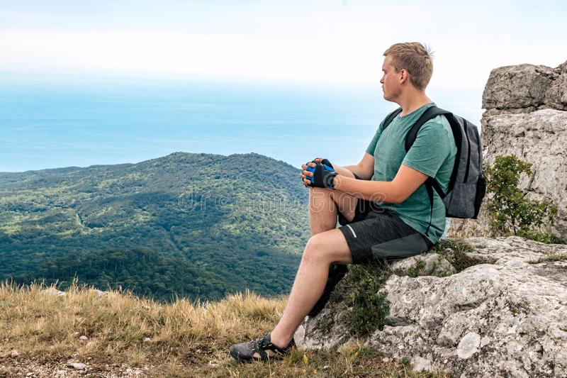 Jonge mens met een rugzak bovenop klip die van mening van aard genieten Bergen en Overzees royalty-vrije stock afbeeldingen