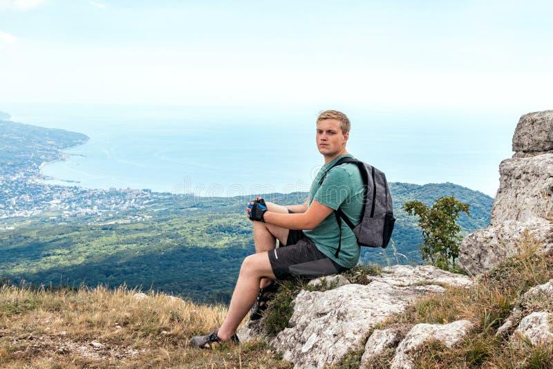 Jonge mens met een rugzak bovenop klip die van mening van aard genieten Bergen en Overzees stock afbeelding