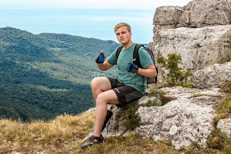 Jonge mens met een rugzak bovenop klip die van mening van aard genieten Bergen en Overzees stock foto's