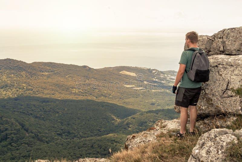 Jonge mens met een rugzak bovenop klip die van mening van aard genieten Bergen en Overzees stock fotografie