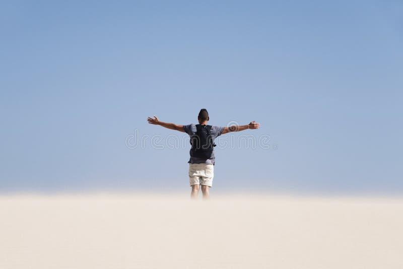 Jonge mens met een rugzak in de woestijn stock foto