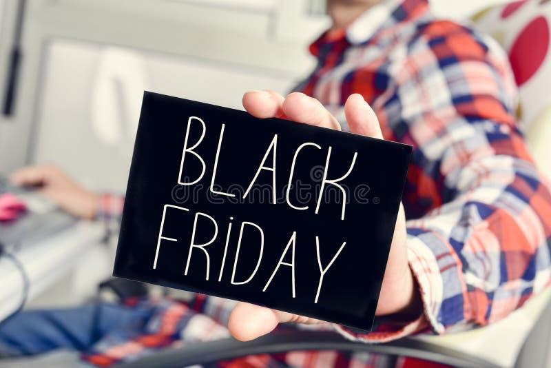 Jonge mens met een uithangbord met de tekst zwarte vrijdag royalty-vrije stock afbeeldingen