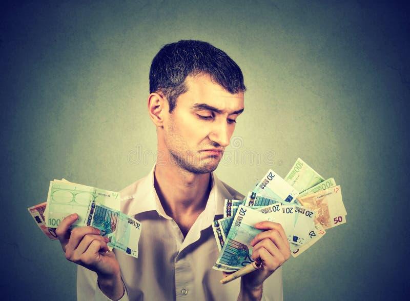 Jonge mens met geldeuro stock fotografie