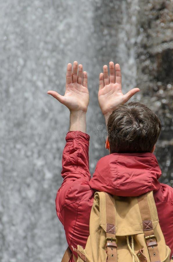 Jonge mens met handen die naar een waterval van water worden opgeheven stock afbeelding