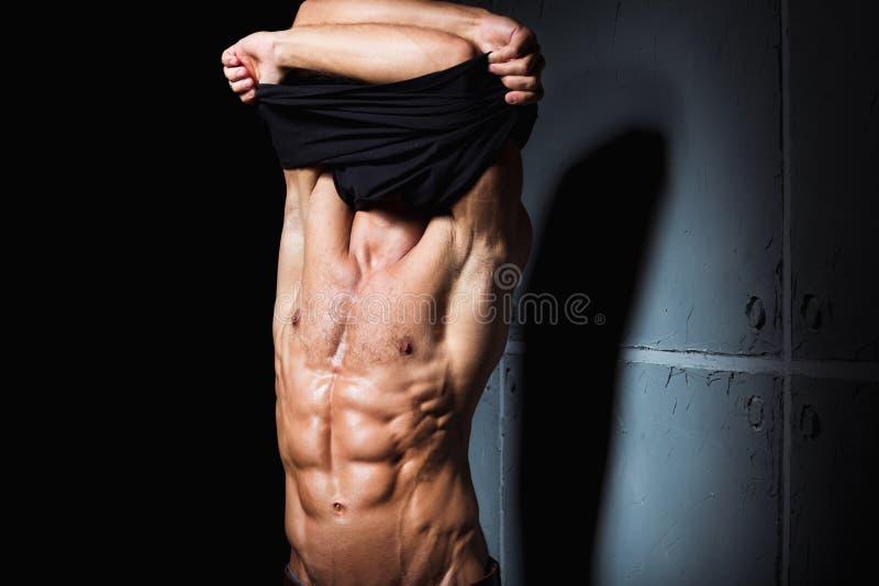 Jonge mens met het perfecte lichaam ontdoen van stock foto's