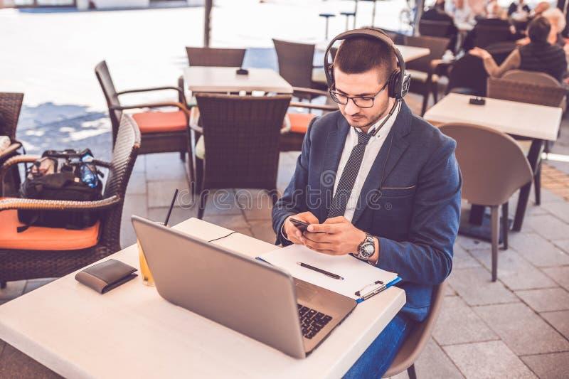 Jonge mens met hoofdtelefoons en glazen die smartphone en laptop computer in straatkoffie met behulp van royalty-vrije stock afbeelding