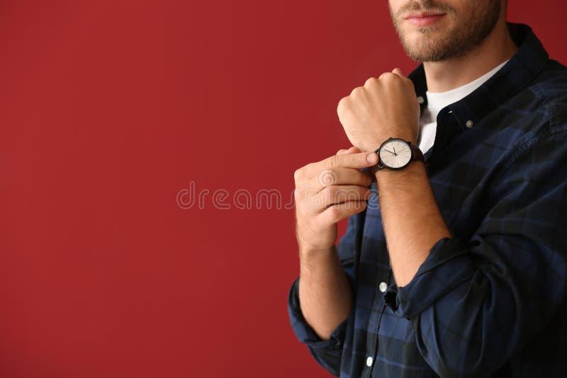 Jonge mens met horloge op kleurenachtergrond stock foto