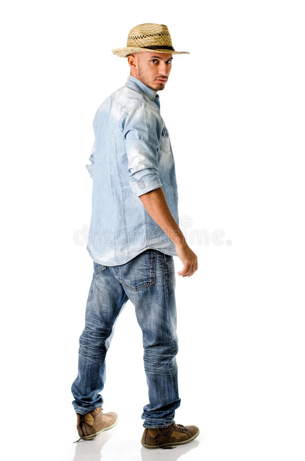 In jonge mens met jeans, denimoverhemd en strohoed stock fotografie
