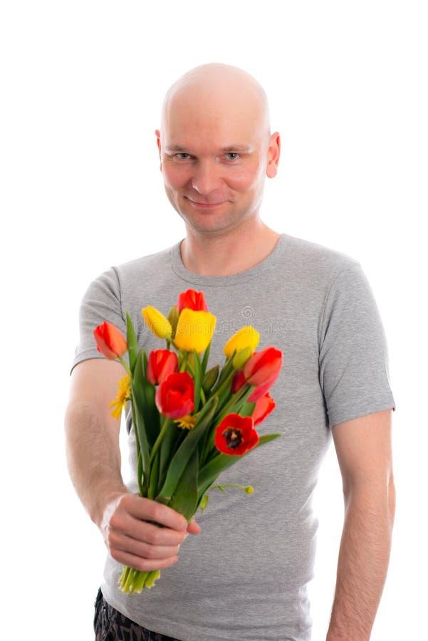 Jonge mens met kale hoofd en bos van tulpen royalty-vrije stock fotografie