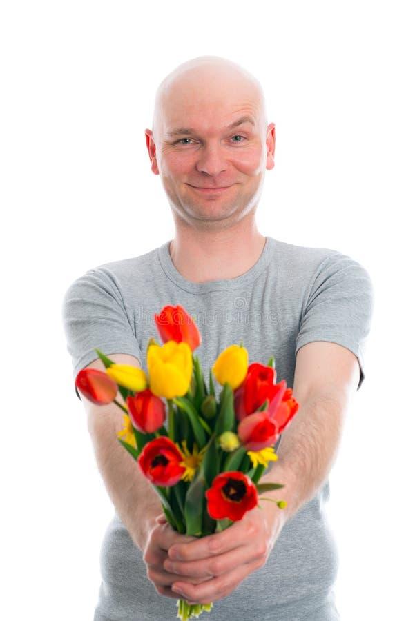 Jonge mens met kale hoofd en bos van tulpen stock foto