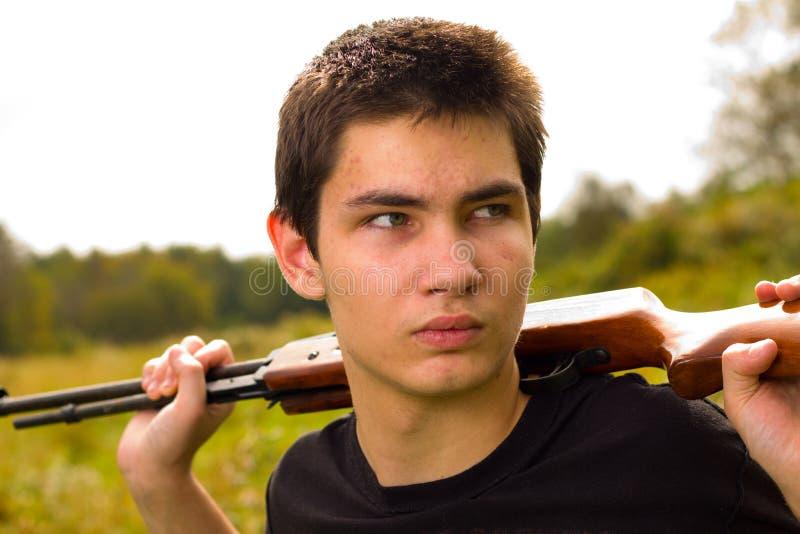 Jonge mens met kanon of geweer stock foto's