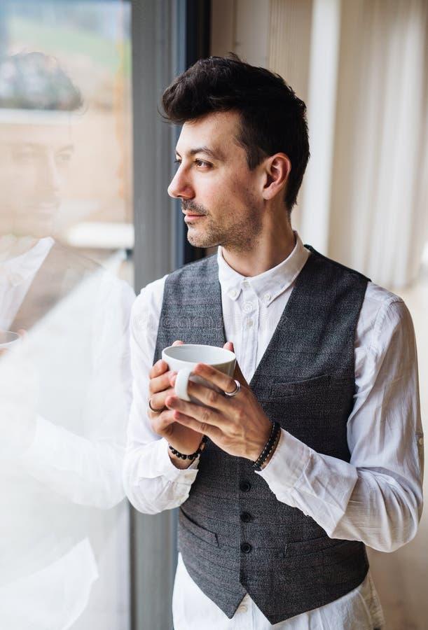 Jonge mens met koffie die zich door het venster bevinden De ruimte van het exemplaar stock afbeelding