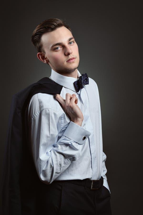 Jonge mens met kostuum en vlinderdas royalty-vrije stock afbeelding