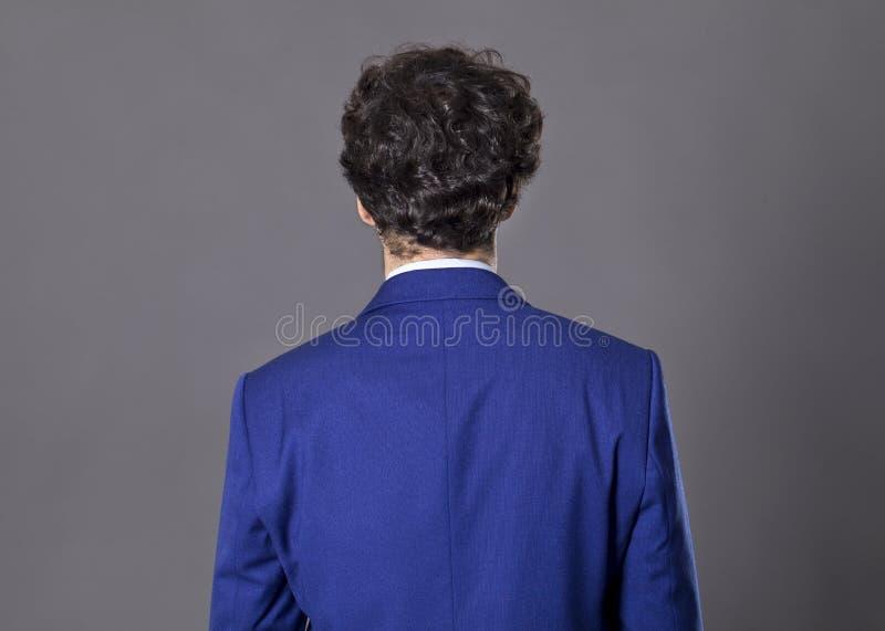 Jonge mens met krullend haar die zich terug naar camera bevinden stock foto