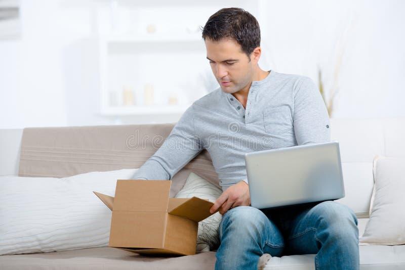 Jonge mens met laptop computer het openen pakketdoos stock foto's