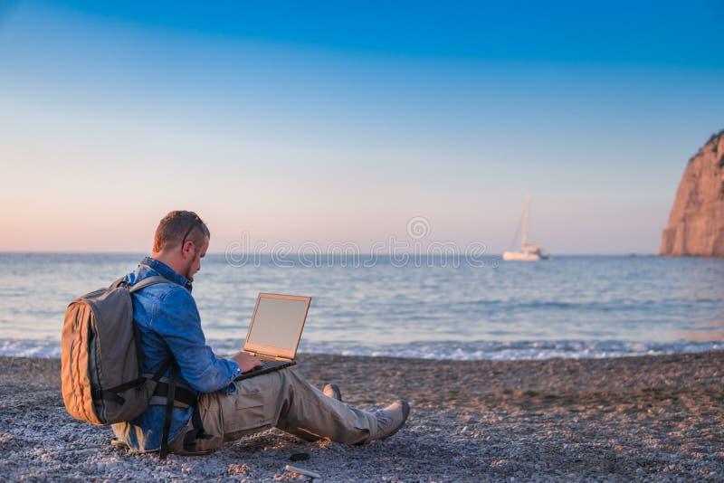 Jonge mens met laptop die aan het strand werken Vrijheid, het verre werk, freelancer, technologie, van Internet, van de reis en v stock foto