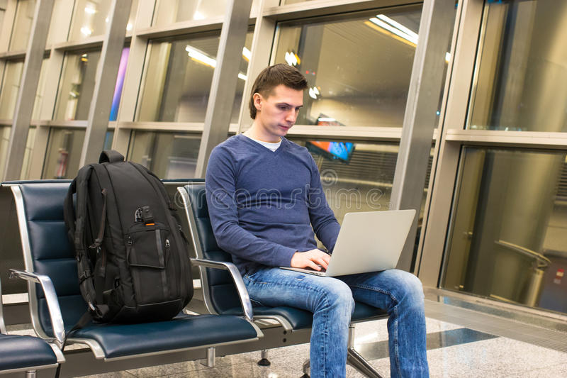 Jonge mens met laptop en rugzak bij luchthaven stock fotografie