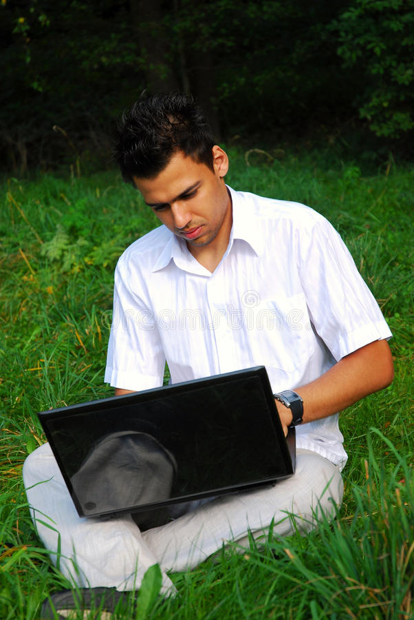 Jonge mens met laptop op het gras stock afbeelding