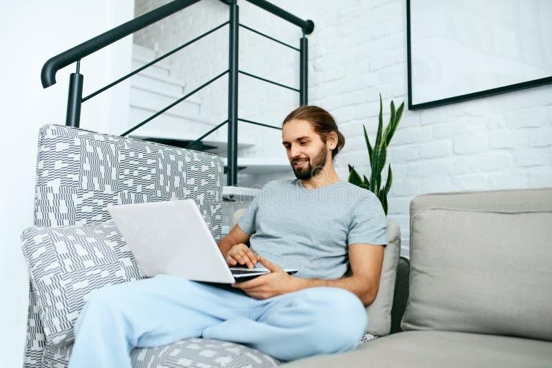 Jonge mens met laptop thuis stock afbeelding