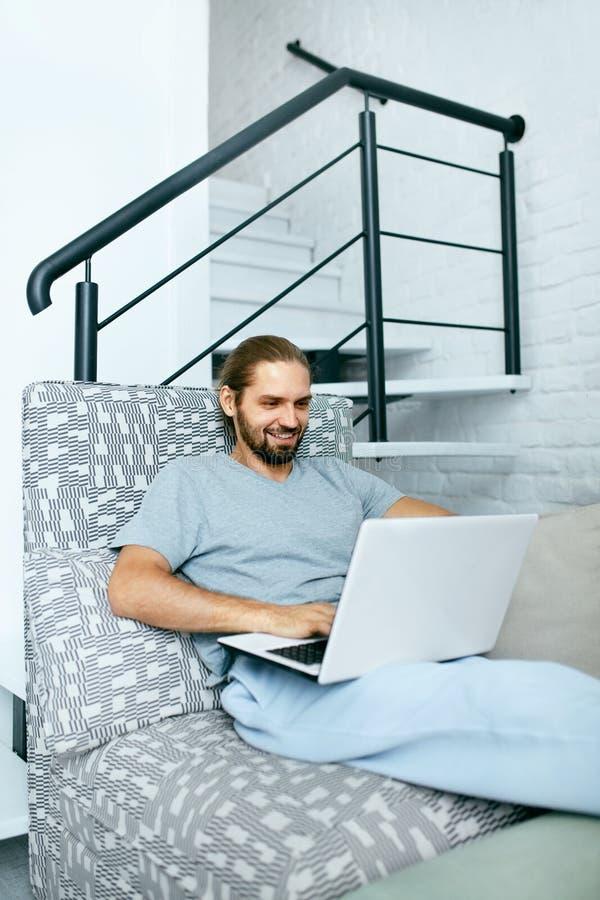 Jonge mens met laptop thuis stock afbeeldingen