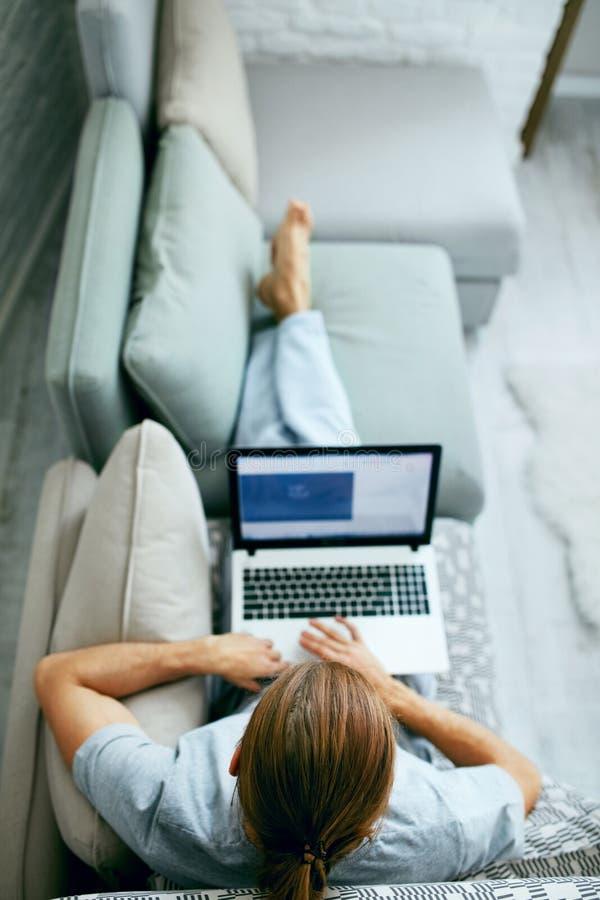 Jonge mens met laptop thuis royalty-vrije stock fotografie
